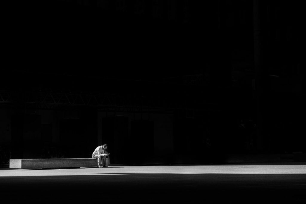 a lone person grieving black and white