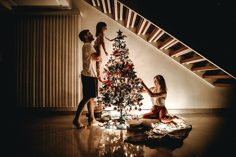 a family trimming a christmas tree