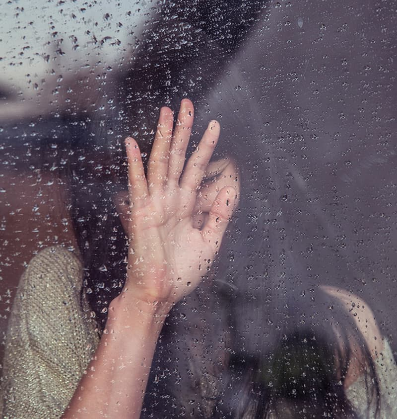 Woman standing next to window in the rain