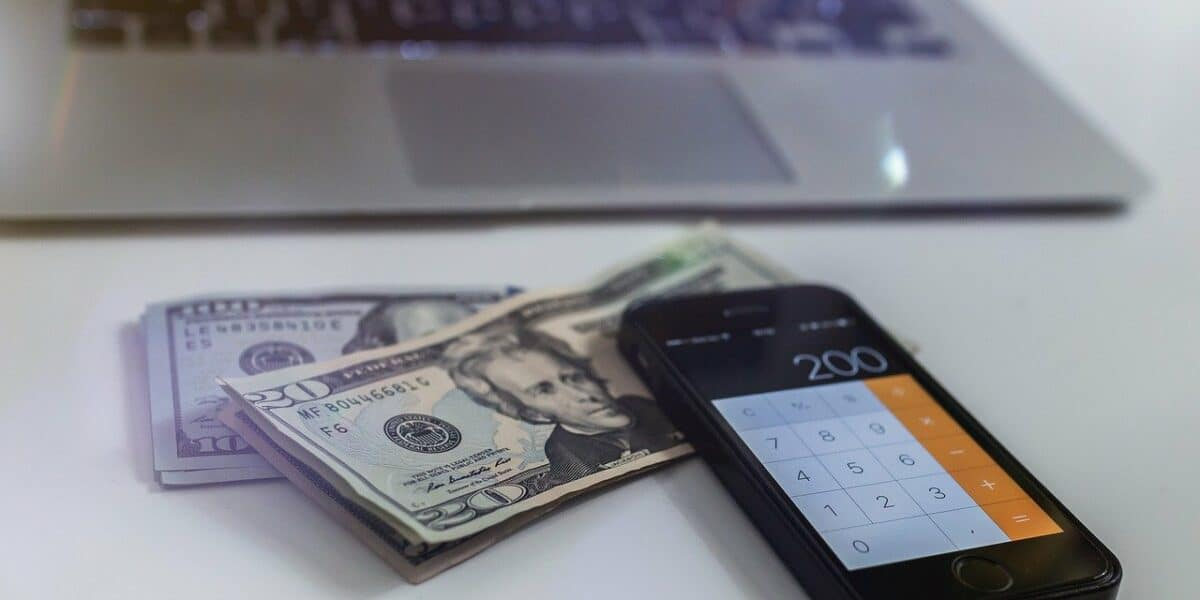 laptop and phone with cash