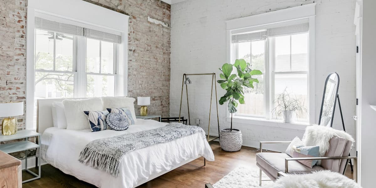 Light and bright bedroom with exposed brick walls, wood floors and luxurious furnishing in Nashville photo shoot location rental