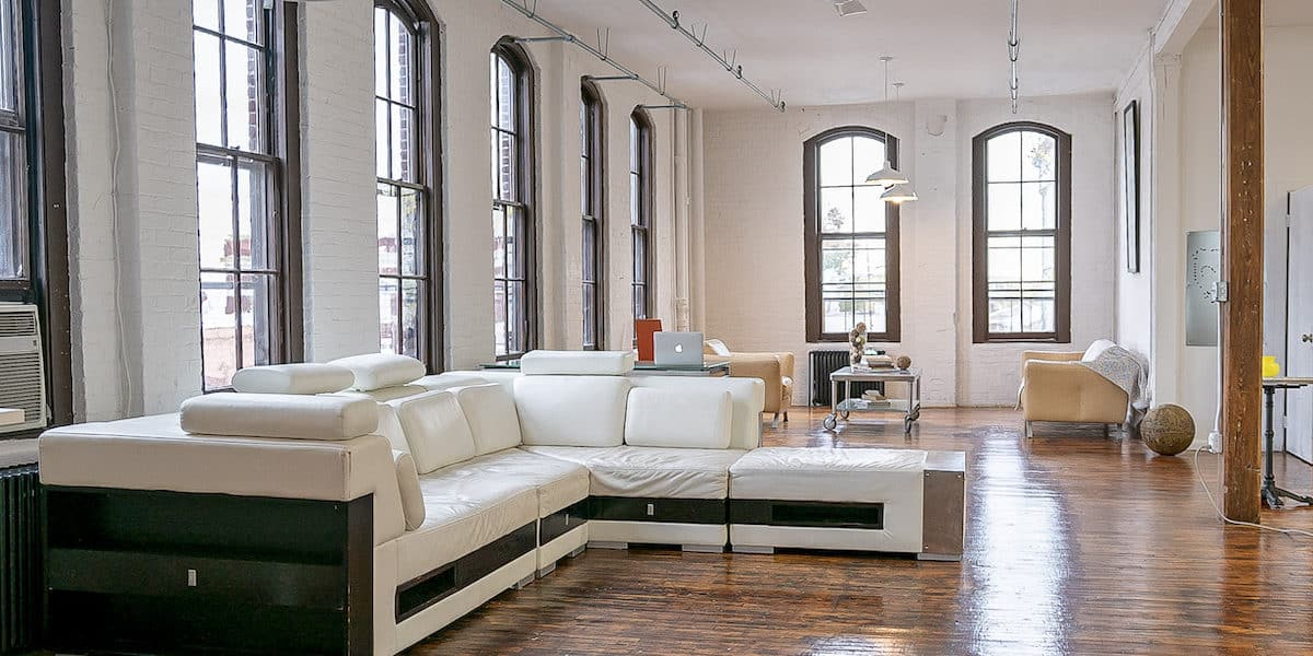 Large loft photography rental space with wooden floors, tall windows and white leather couches
