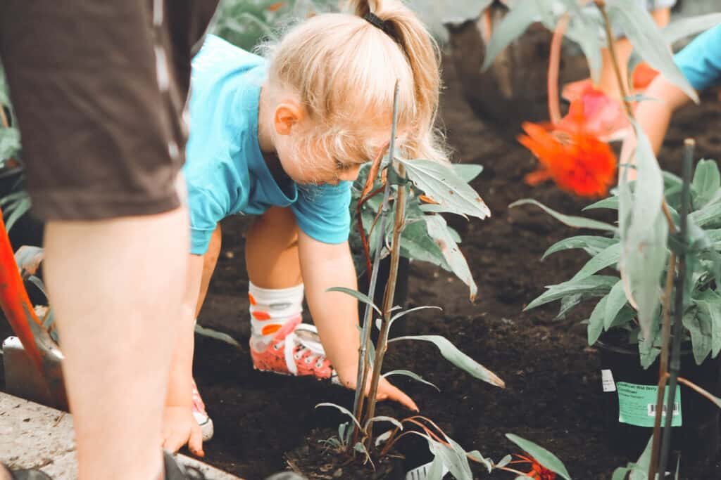 a child helping plant a garden for charity